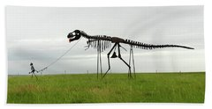 Skeletal Man Walking His Dinosaur Statue Beach Towel