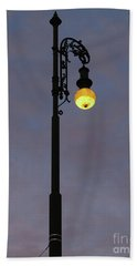 Beach Towel featuring the photograph Street Lamp Shining At Dusk by Michal Boubin