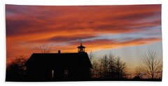 Sunsetting Behind The Historic Schoolhouse. Beach Towel