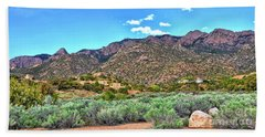 Beach Towel featuring the photograph The Sandias by Gina Savage