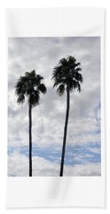 Twin Palm Trees Silhouetted Against Cloudy Blue Sky Beach Towel