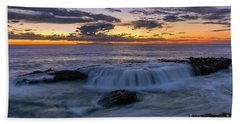 Wave Over The Rocks Beach Towel by Eddie Yerkish