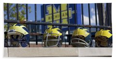 Beach Towel featuring the photograph Wolverine Helmets Of Different Eras On Stadium Wall by Michigan Helmet
