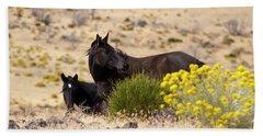 Two Wild Black Horses Among Yellow Flowers Beach Towel