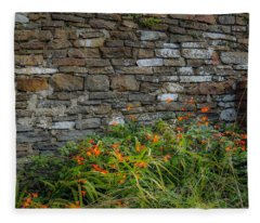 Orange Wildflowers Against Stone Wall Fleece Blanket