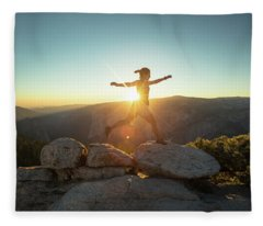 Person Leaping Along Rocks At Sunset Fleece Blanket