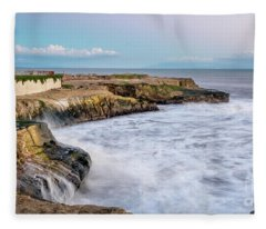 Long Exposure Of Waves Against The Cliff With Lighthouse In Shot Fleece Blanket