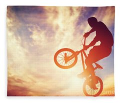 Man Riding A Bmx Bike Performing A Trick Against Sunset Sky Fleece Blanket