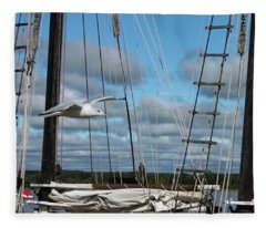 Seagull Flying Past Rigging And Ropes Of Sailing Vessel On Stomy Day With Shore And Cloudy Sky In Ba Fleece Blanket