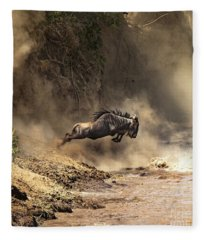 Wildebeest Leaps From The Bank Of The Mara River Fleece Blanket