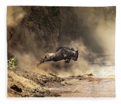 Wildebeest Leaps From The Bank Of The Mara River Fleece Blanket