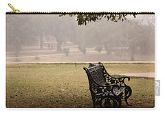 Carry-all Pouch featuring the photograph A Wrought Iron Black Metal Bench Under A Tree In The Qutub Minar Compound by Ashish Agarwal