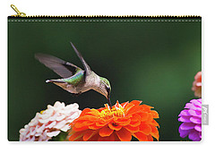 Carry-all Pouch featuring the photograph Hummingbird In Flight With Orange Zinnia Flower by Christina Rollo