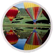 Round Beach Towel featuring the photograph Reflection Of Hot Air Balloons by Panoramic Images