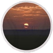 The Setting Sun In The Distance With Clouds Round Beach Towel