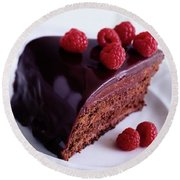 A Chocolate Pecan Cake With Raspberries On Top Round Beach Towel