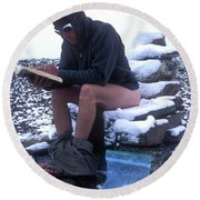 A Man Reads While Using A Snow-covered Round Beach Towel