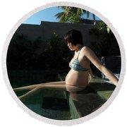 A Pregnant Woman Enjoying The Sun While Round Beach Towel