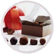 A Still Life Photo Of Gourmet Chocolates Round Beach Towel