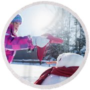 A Young Girl Building A Snowman Round Beach Towel