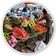 Fruit And Vegetable Seller Tends To His Cart Outside Empress Market Karachi Pakistan Round Beach Towel