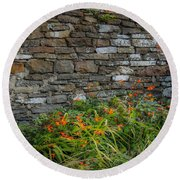 Orange Wildflowers Against Stone Wall Round Beach Towel