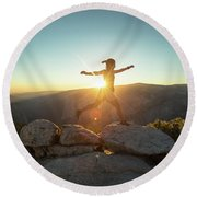 Person Leaping Along Rocks At Sunset Round Beach Towel