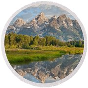 Teton Range Reflected In The Snake River Round Beach Towel by Jeff Goulden