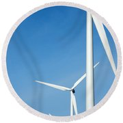 Three Mighty Windmills In A Row Against A Blue Sky. Round Beach Towel