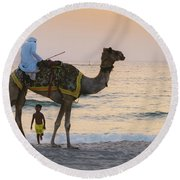 Little Boy Stares In Amazement At A Camel Riding On Marina Beach In Dubai, United Arab Emirates -  Round Beach Towel