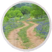 A Dirt Road Lined By Blue Bonnets Of Texas Round Beach Towel