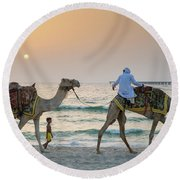 A Little Boy Stares In Amazement At A Camel Riding On Marina Beach In Dubai, United Arab Emirates Round Beach Towel