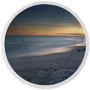 A Sandy Shoreline At Sunset Round Beach Towel