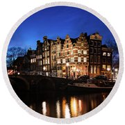Round Beach Towel featuring the photograph Amsterdam Canal Houses Illuminated At Dusk by IPics Photography