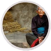An Old Woman In Bhaktapur Round Beach Towel
