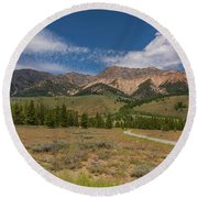 Approaching The Sawtooth Mountains Round Beach Towel by Brenda Jacobs