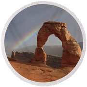 Round Beach Towel featuring the photograph Delicate Arch And Rainbow by Marie Leslie