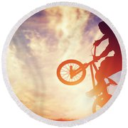 Man Riding A Bmx Bike Performing A Trick Against Sunset Sky Round Beach Towel