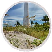 Round Beach Towel featuring the photograph Pelican Flying Over Cape Florida Lighthouse by Justin Kelefas