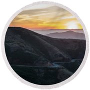 Road On The Edge Of The Mountain With Sunrise In The Background Round Beach Towel