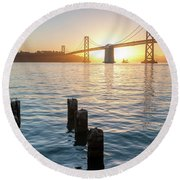 Six Pillars Sticking Out The Water With Bay Bridge In The Backgr Round Beach Towel