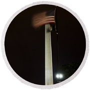 Round Beach Towel featuring the photograph Washington Monument At Night With Flag by Angela DeFrias