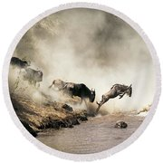 Wildebeest Leaping In Mid-air Over Mara River Round Beach Towel