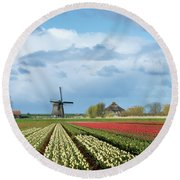 Round Beach Towel featuring the photograph Windmill With Tulip Flower Fields In The Countryside by IPics Photography