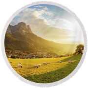 Black Head Sheep Graze By A Church In Alps Round Beach Towel