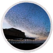 Starlings At Dusk Over Aberystwyth Pier Round Beach Towel