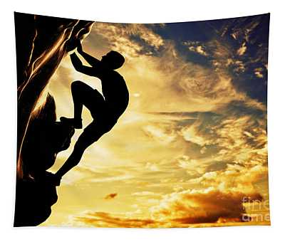 A Silhouette Of Man Free Climbing On Rock Mountain At Sunset Tapestry
