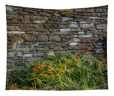 Orange Wildflowers Against Stone Wall Tapestry