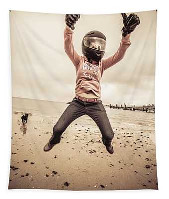 Woman Wearing Helmet And Gloves Jumping On Beach Tapestry