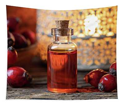 A Bottle Of Rose Hip Seed Oil With Dried Rose Hips Tapestry